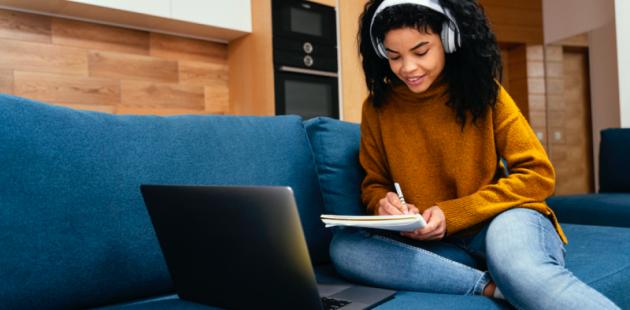 Adolescente sentada en un sillón y utilizando una laptop.