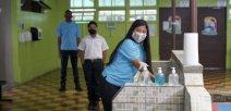 Imagen muestra a estudiantes con lavado de manos y distanciamiento